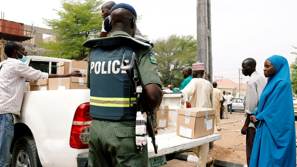 A police officer oversees staff loading boxes onto a truck during the distribution of election materials at the INEC office in Yola, in Adamawa State, Nigeria, 15 February 2019