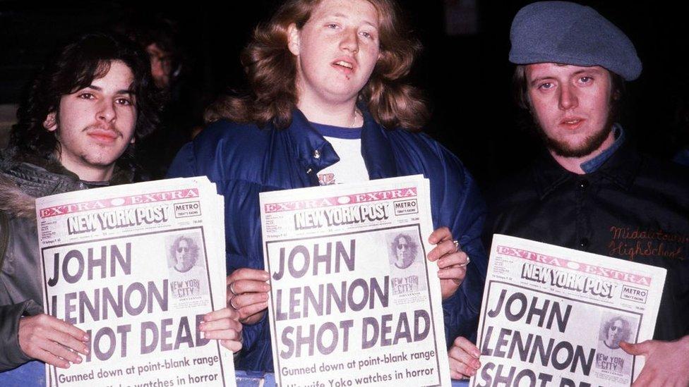 Tres jóvenes sostienen tres periódicos con el titular que anuncia la muerte de John Lennon.