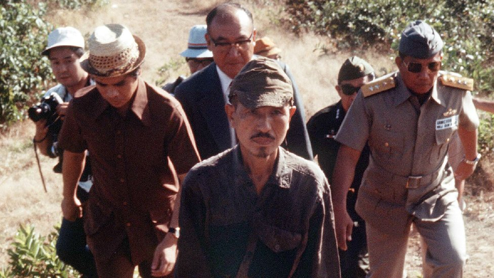 Lieutenant Hiroo Onoda walks from the jungle with a group behind him