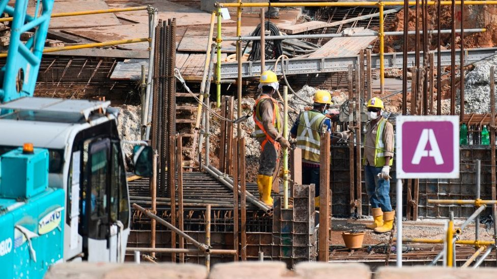 Migrant workers work at a construction site in Singapore on August 20, 2020.