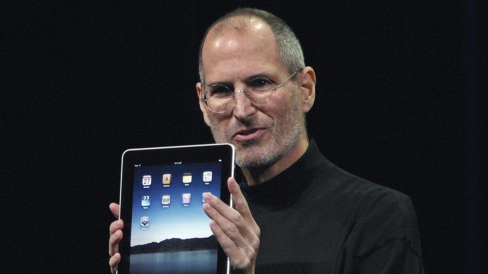 Steve Jobs holding an iPad on stage