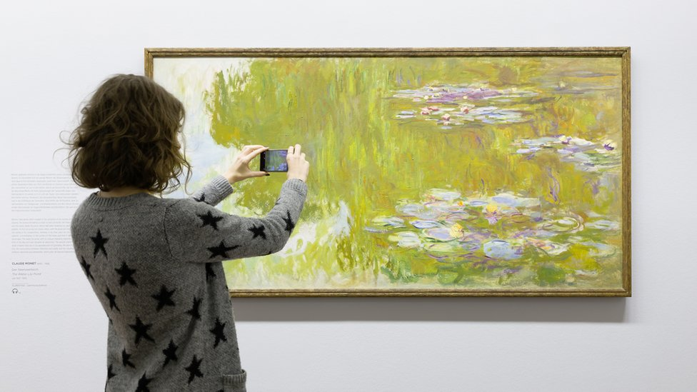 Woman looking at Money water lilies painting through AR app