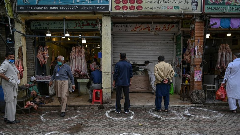 Customers stand in circles on ground, as part of social distancing measures, outside shops in Islamabad