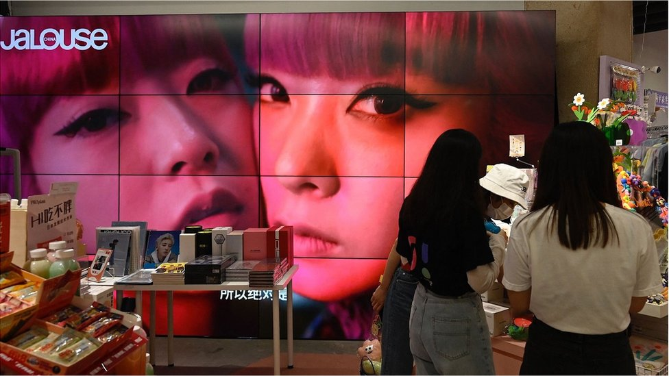 A screen shows a video of overseas celebrity idols at a fan merchandise store at a shopping mall in Beijing on September 2, 2021.