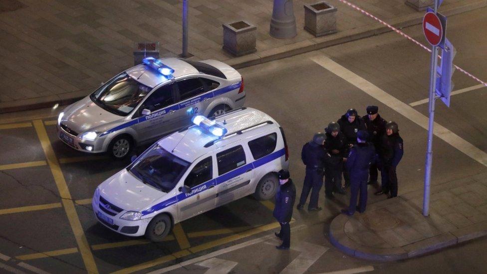 مجموعة من رجال الشرطة يقفون بجوار سيارتي شرطة.