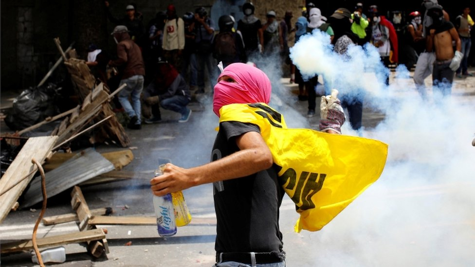 A demonstrator prepares to throw a tear gas canister during a strike called to protest against Venezuelan President Nicolas Maduro's government in Caracas, Venezuela on 26 July, 2017.