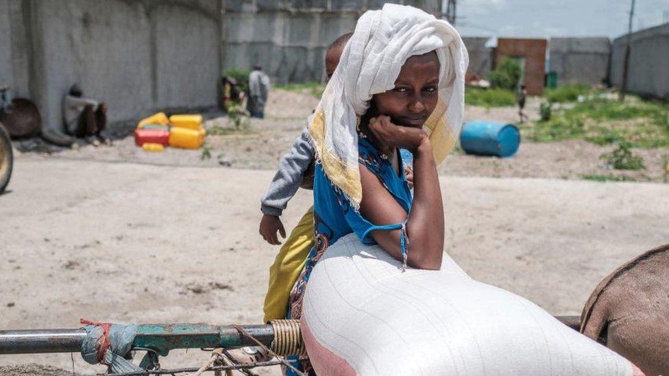 سيدة تحمل طفلها وتنتظر توزيع المساعدات