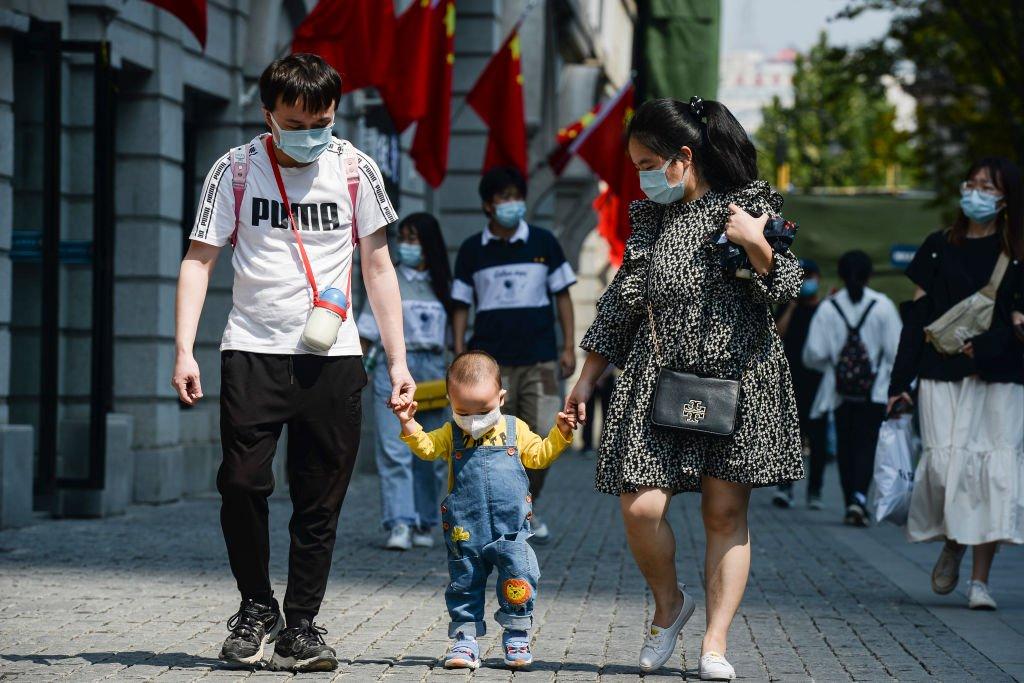 Una familia en Wuhan caminando con mascarillas