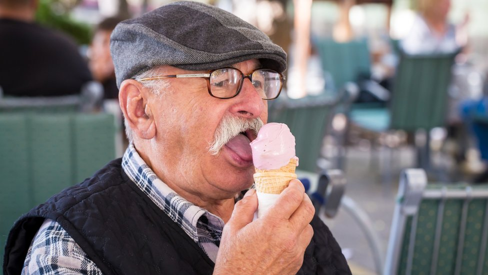 An older man eats an ice cream