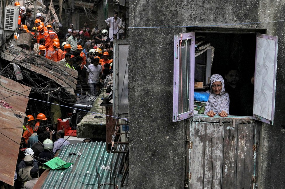 A resident looks out of her house as rescue workers search for survivors at the site of a collapsed building in Mumbai