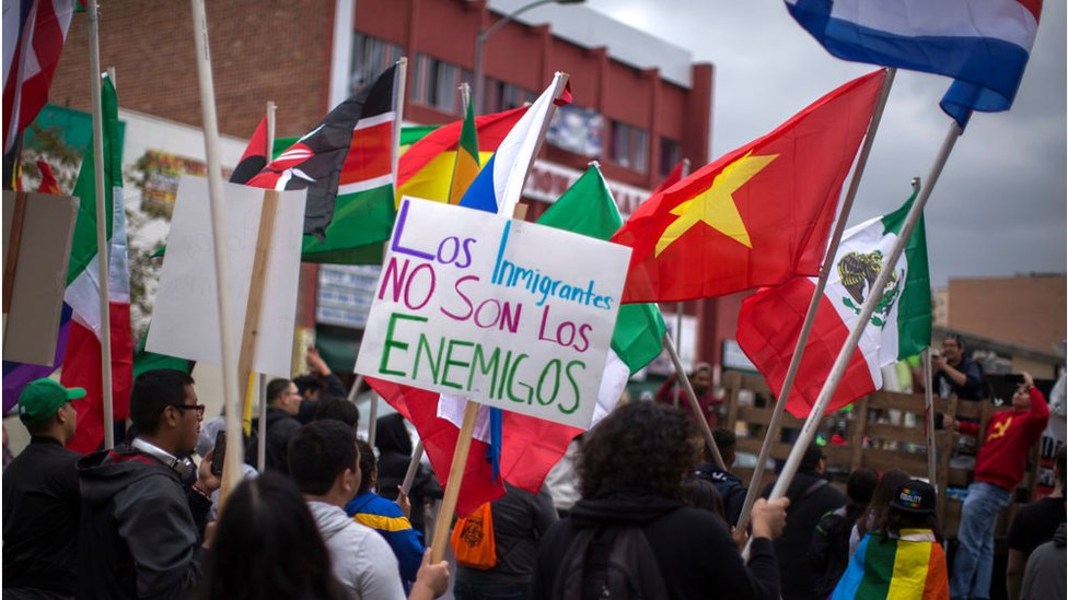 "A protestor holds a sign reading ""Los immigrantes no son los enemigos"", immigrants are not the enemies"