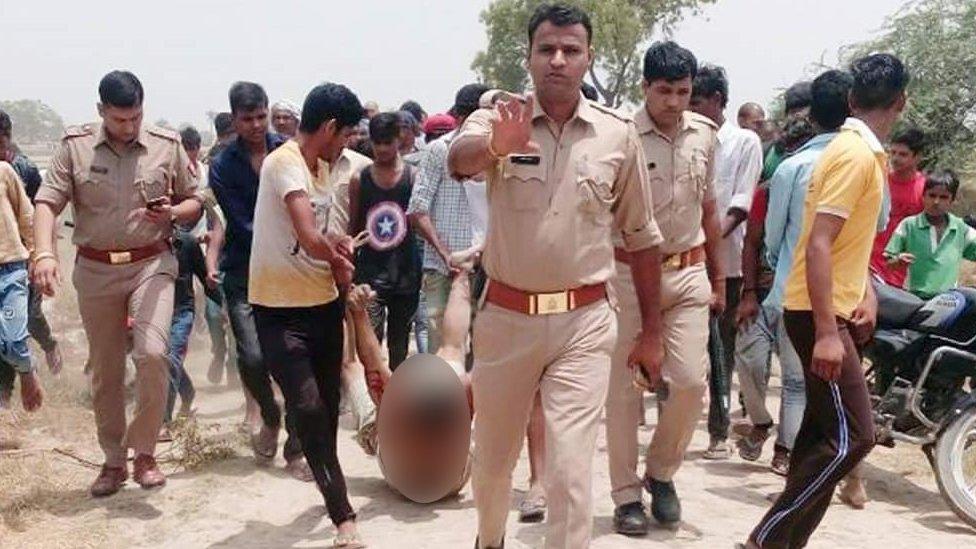 صورة الضحية يجره اثنان وحولهم أناس ورجال شرطة