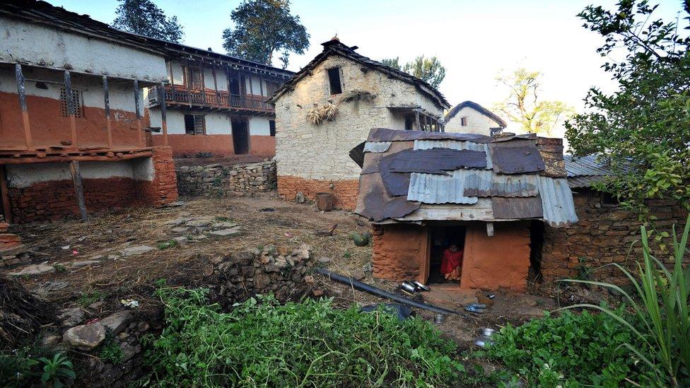 "In this file photo taken on November 23, 2011 a Nepali teenage girl sits inside a ""chhaupadi house"" in Achham village, some 800km west of Kathmandu,"