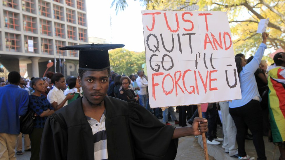 "A protesters in Harare, Zimbabwe, dressed in a graduation gown and cap holding a sign reading ""Just Quit And Go I'll Fogive U"" - Wednesday 3 August 2016"