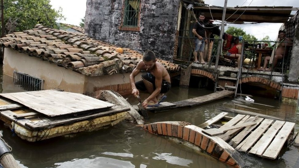 A man works near partially submerged houses in Asuncion, Paraguay. Photo: 20 December 2015