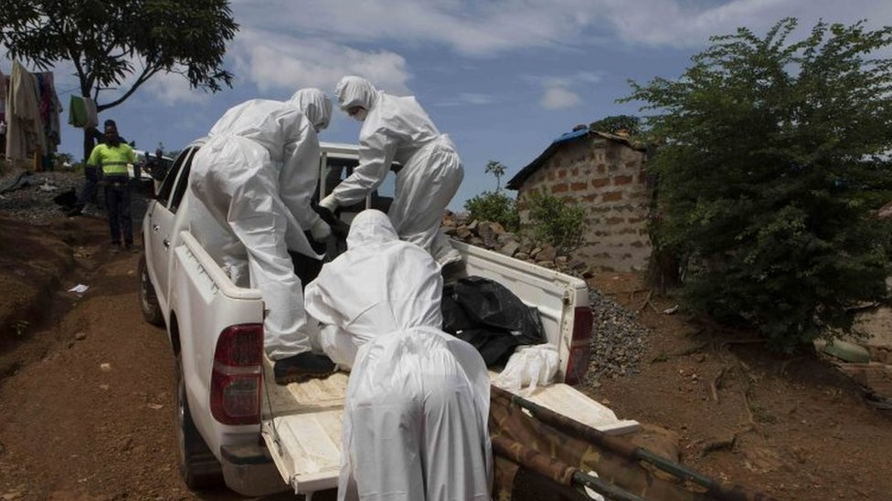 A burial team wearing protective clothing remove a body of a person suspected of having died of the Ebola virus in Freetown, Liberia (28 September 2014)