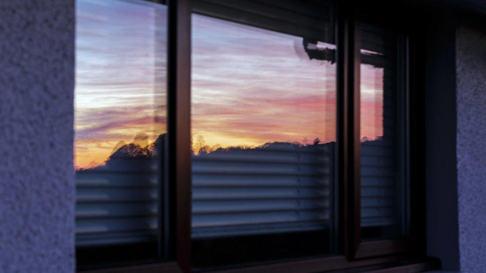 Reflexo de por do sol em janela