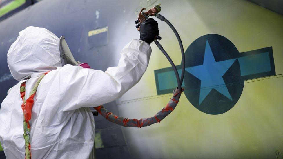 An airman based at RAF Lakenheath paints around a National Star insignia