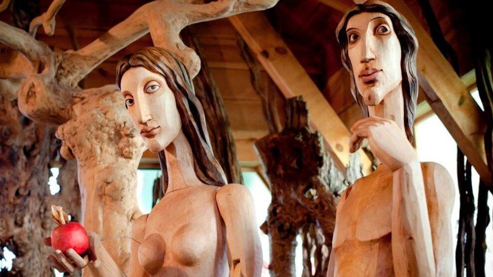 Adam and Eve sculptures have been carved out of wood.
