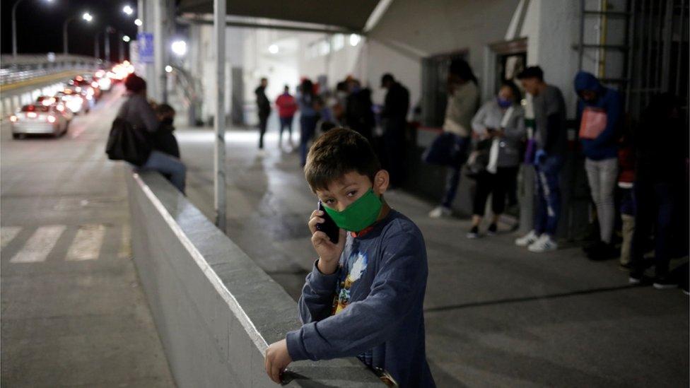 Un niño migrante habla por teléfono el 21 de abril en un paso fronterizo de México a EE.UU. mientras su familia hace la fila para reprogramar sus audiencias de casos de inmigración en EE.UU.