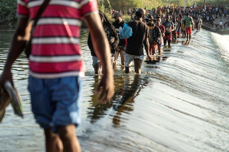 Migrantes que buscan asilo en Estados Unidos caminan por el río Grande cerca del Puente Internacional entre México y Estados Unidos, mientras esperan ser procesados, en Ciudad Acuña, México, el 16 de septiembre de 2021.