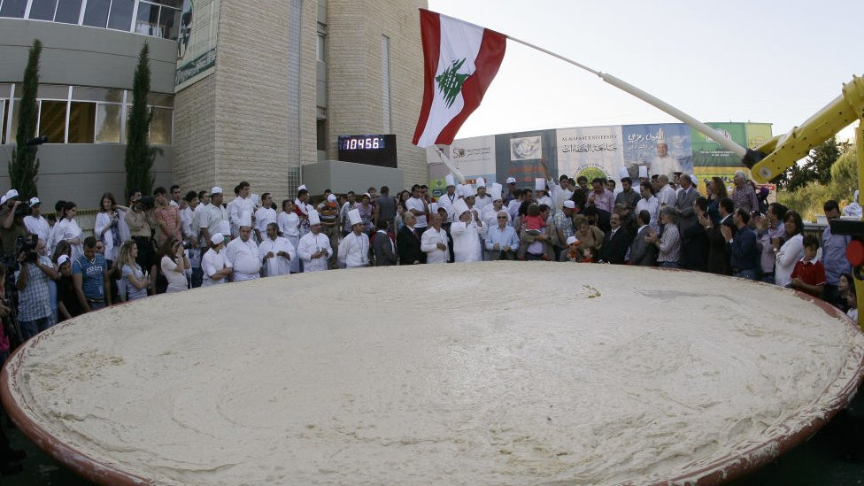 Lebanese chefs celebrate around the largest plate of hummus after setting a new Guinness world record in Beirut on May 8, 2010