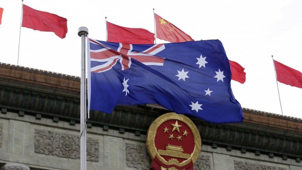 An Australian flag in front of Chinese flags