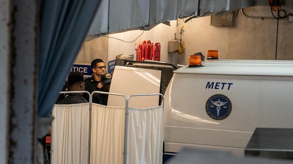 Los oficiales de policía cubren un auto médico forense en la entrada del hospital de Nueva York donde Epstein fue trasladado.