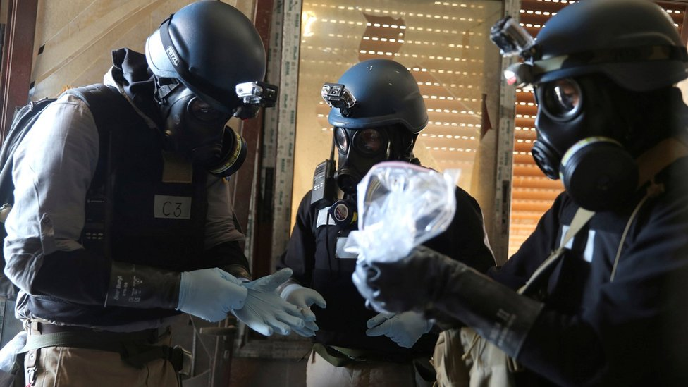 A UN chemical weapons expert, wearing a gas mask, holds a bag containing samples from a site of an alleged chemical weapons attack