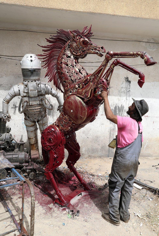 رجل يعمل على تمثال معدني لحصان