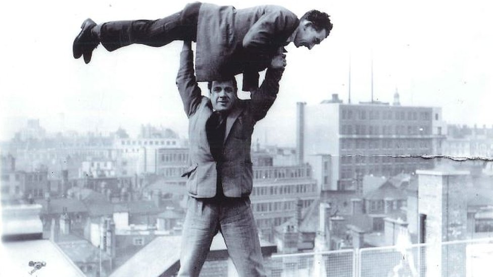 Men stand on the roof of a building in Birmingham