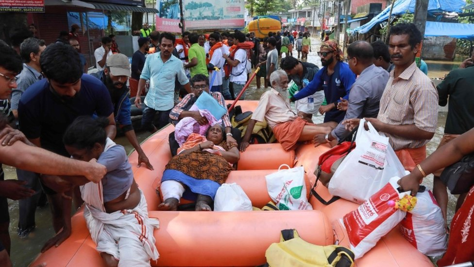 Indian men and women are evacuated by rescue workers using an orange rescue dinghy
