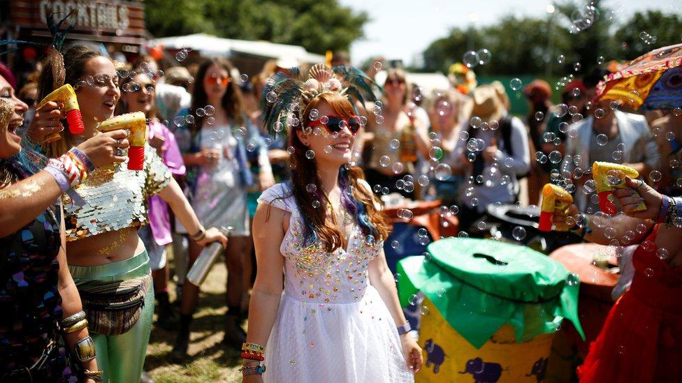 Festival-goers spray bubbles at Glastonbury