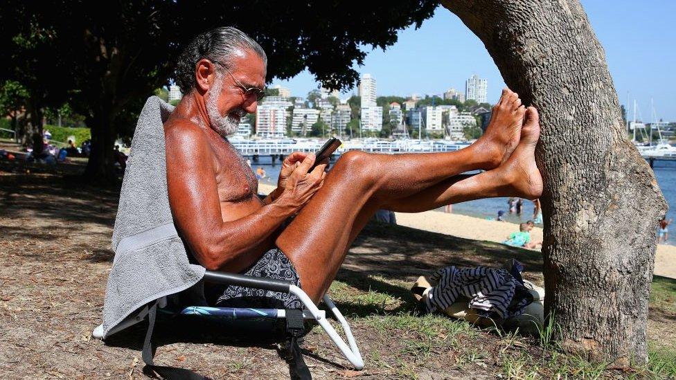 čovek se sunča u Sidneju