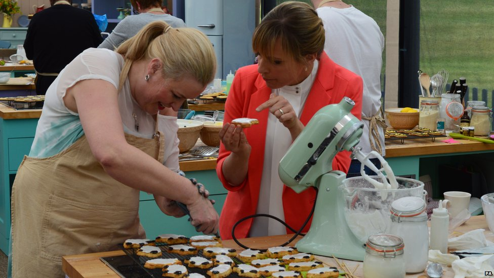Mel Giedroyc helps a Bake Off contestant
