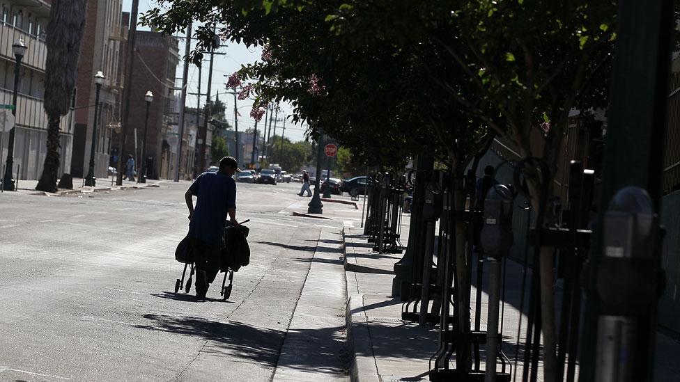 Una persona recoge materiales reciclables en un carrito en las calles de Stockton