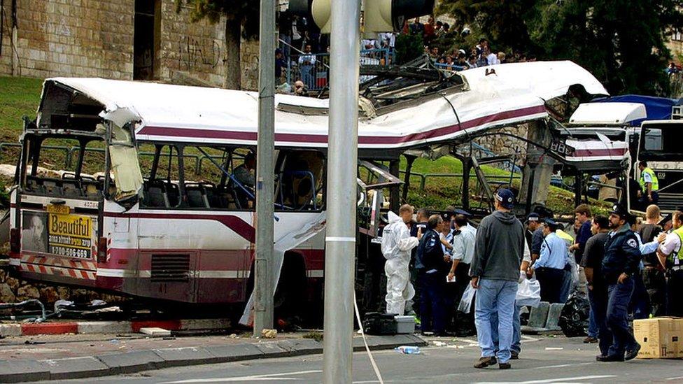 Autoridades israelíes investigan los restos de un autobús tras un ataque con bomba en Haifa, 2001
