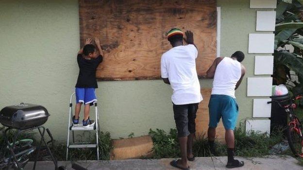 Warga menutup jendela di Port Salerno, Florida, bersiap menghadapi terjangan topan.