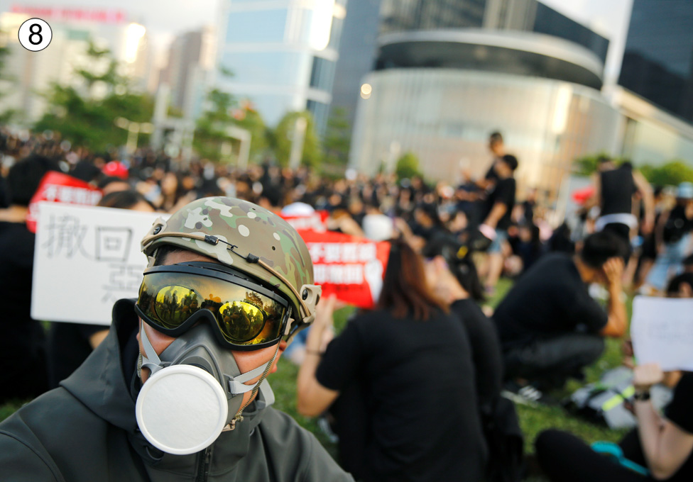 A man in a yellow sun visor and wearing what looks like a gas mask looks at teh camera, while behind him a large crowd of