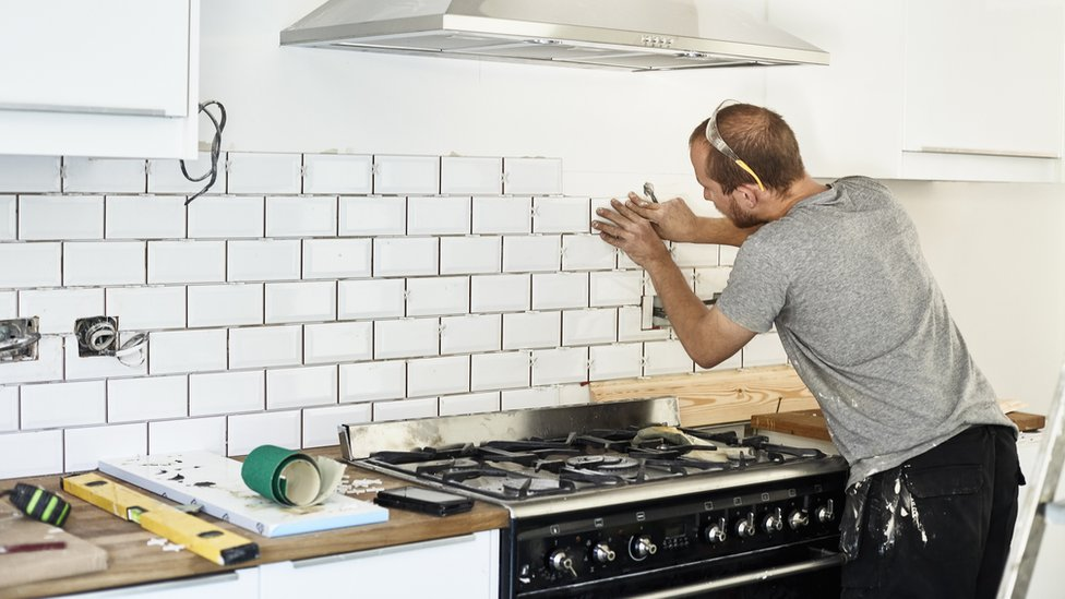 A man working in a new kitchen, a tiler applying tiles to the wall behind the cooker. - stock photo