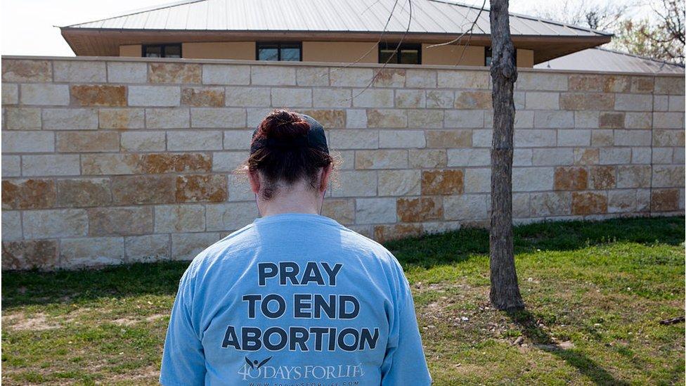 Kürtaj karşıtı bir kadın Teksas'ta bir klinik önünde dua ediyor.