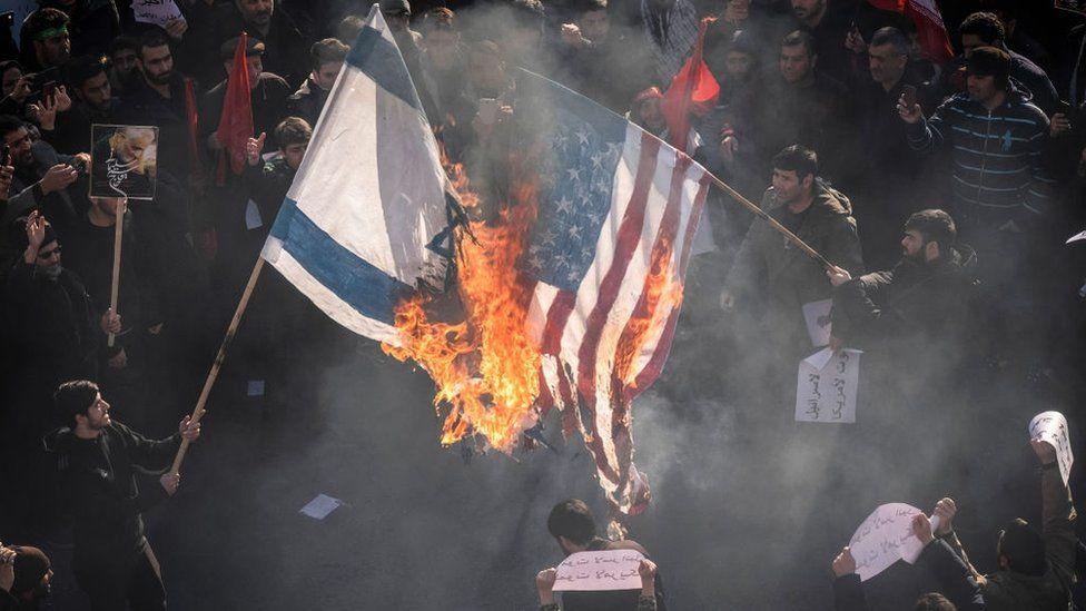 Quema de las banderas israelí y estadounidenses durante una protesta en Irán.