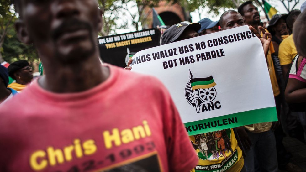 Des membres de l'African National Congress (ANC) manifestent devant la Cour constitutionnelle pour protester contre la libération conditionnelle accordée à Janusz Walus, l'assassin du héros anti-apartheid Chris Hani
