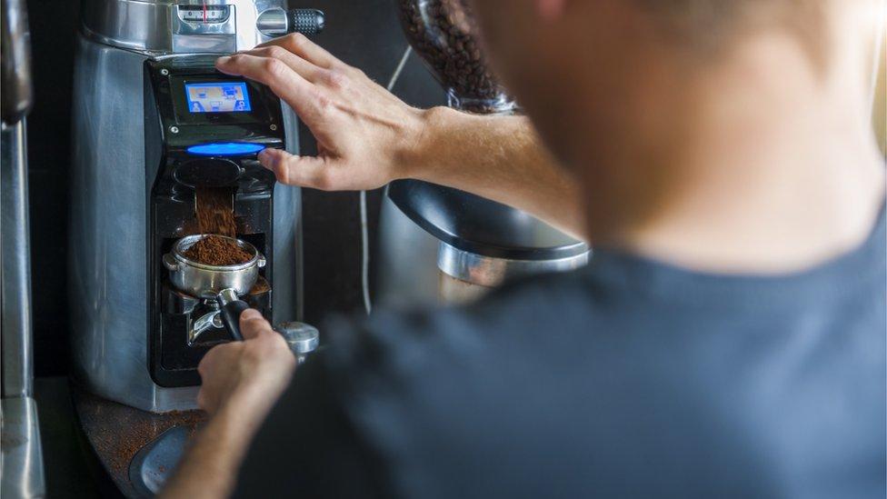A barista makes a coffee