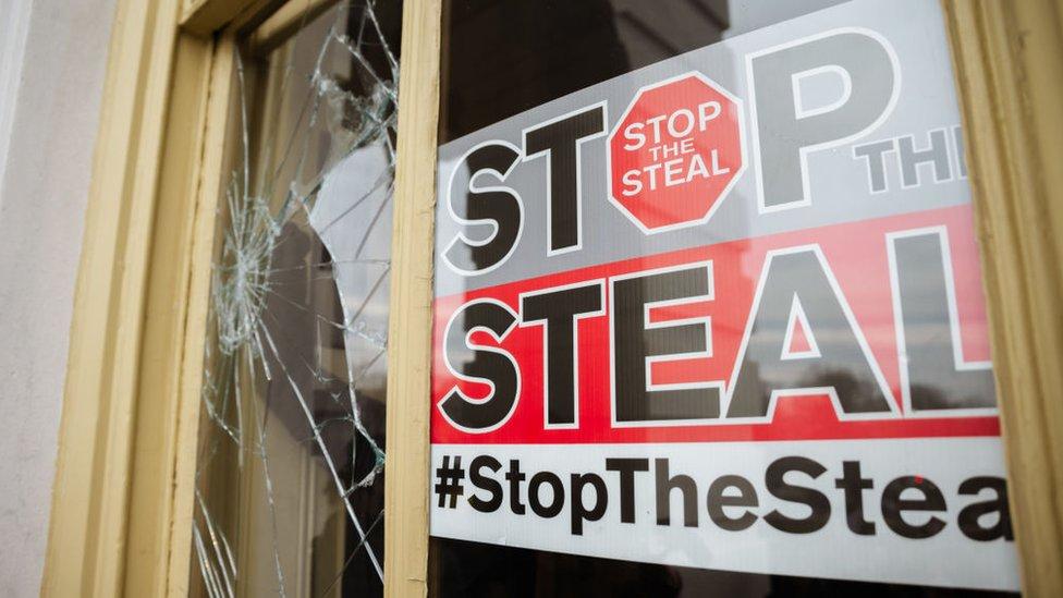 """Una ventana rota con el mensaje """"Stop the steal""""."""
