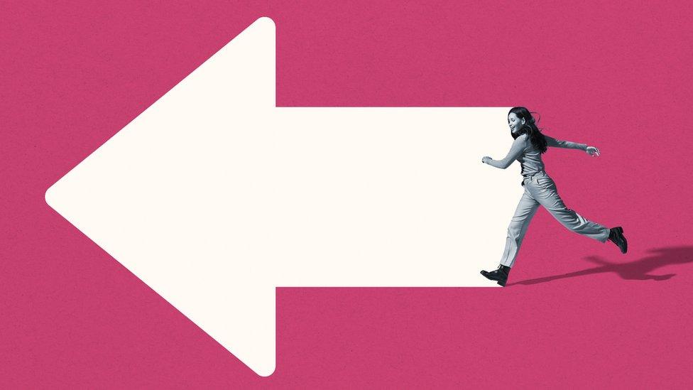 Una mujer camina en dirección a una flecha.
