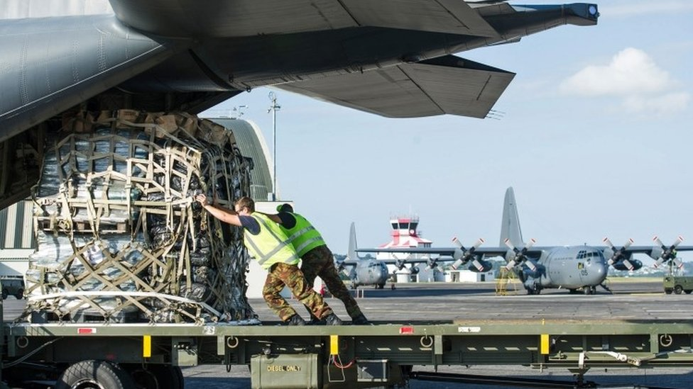 Royal New Zealand Air Force personnel load aid supplies for Cyclone Winston relief on board a C-130 Hercules transport aircraft bound for Fiji (22 February 2016)