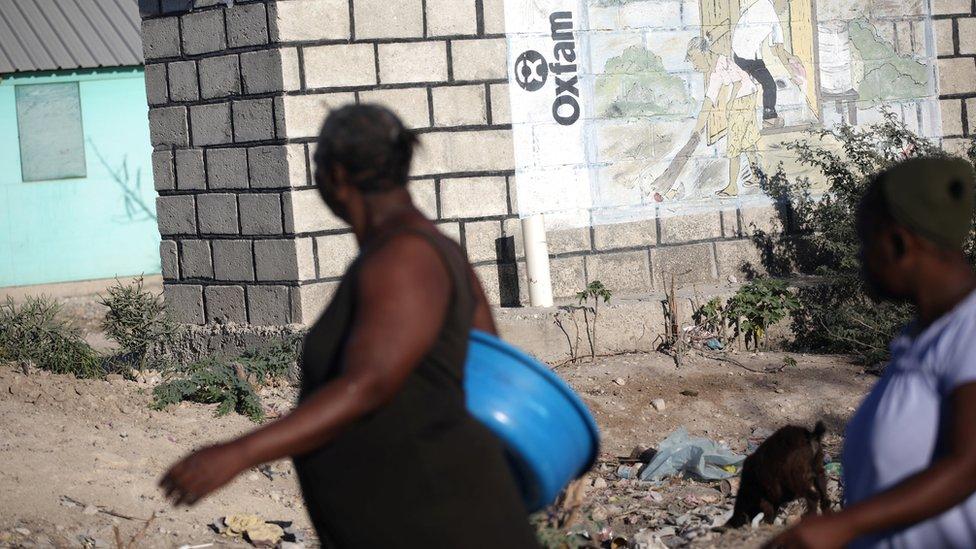 Women walking past Oxfam mural in Haiti in 2018