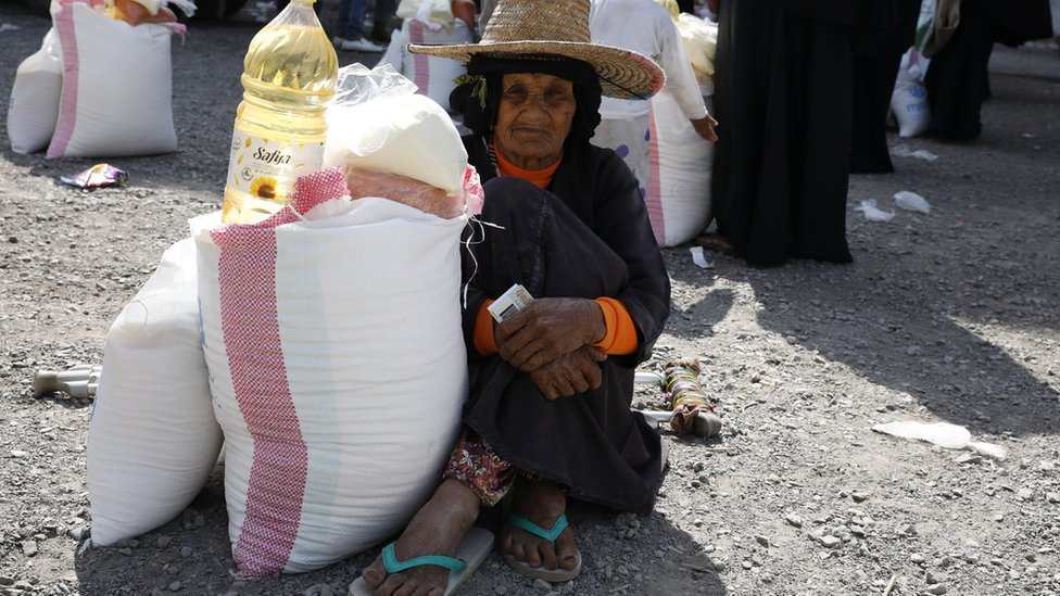 An elderly Yemeni woman gets her family's food ration provided by a local aid group, Mona Relief Yemen, in the western port city of Hudaydah, Yemen, (7 January 2021)