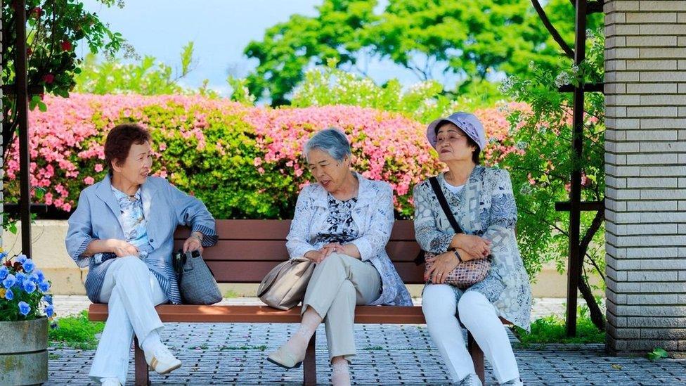 Tres mujeres de la tercera edad sentadas en un banco.